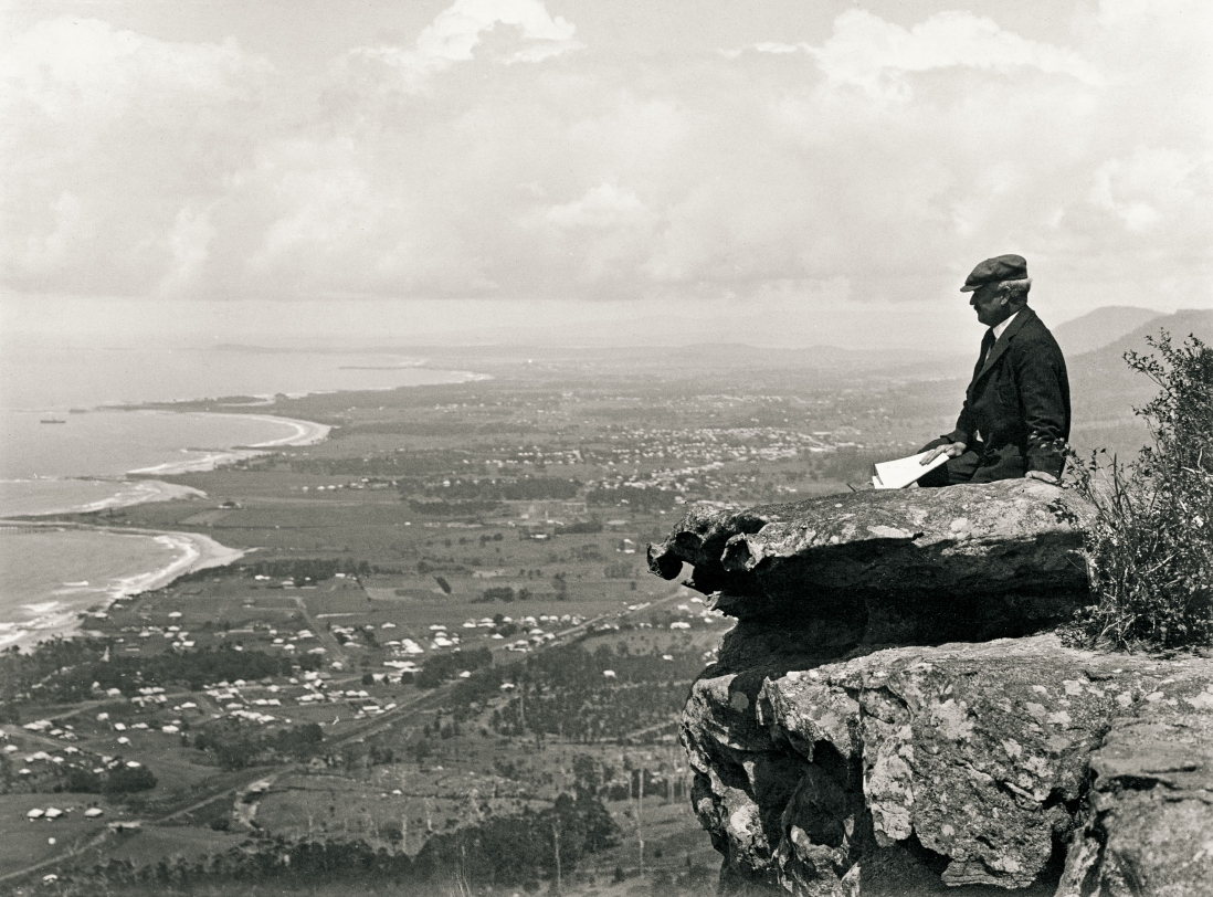 Man sits on a rock at the edge of an escarpment with a dramatic view showing a sweeping coastline, fields and dotted with houses.