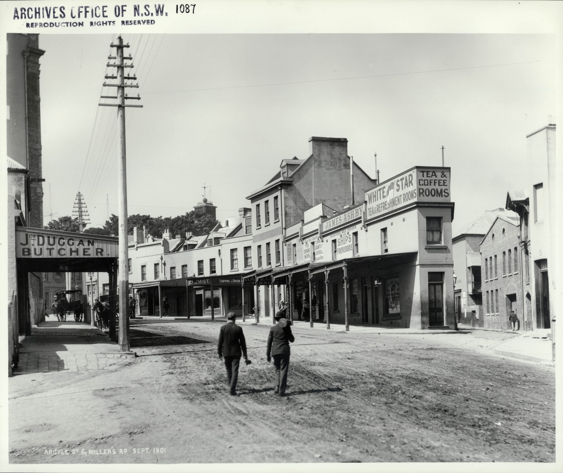 Photograph of street scene showing a row of two storey terraces. The street is lined by awnings indicating shops. Two men walk down the centre of the wide street.