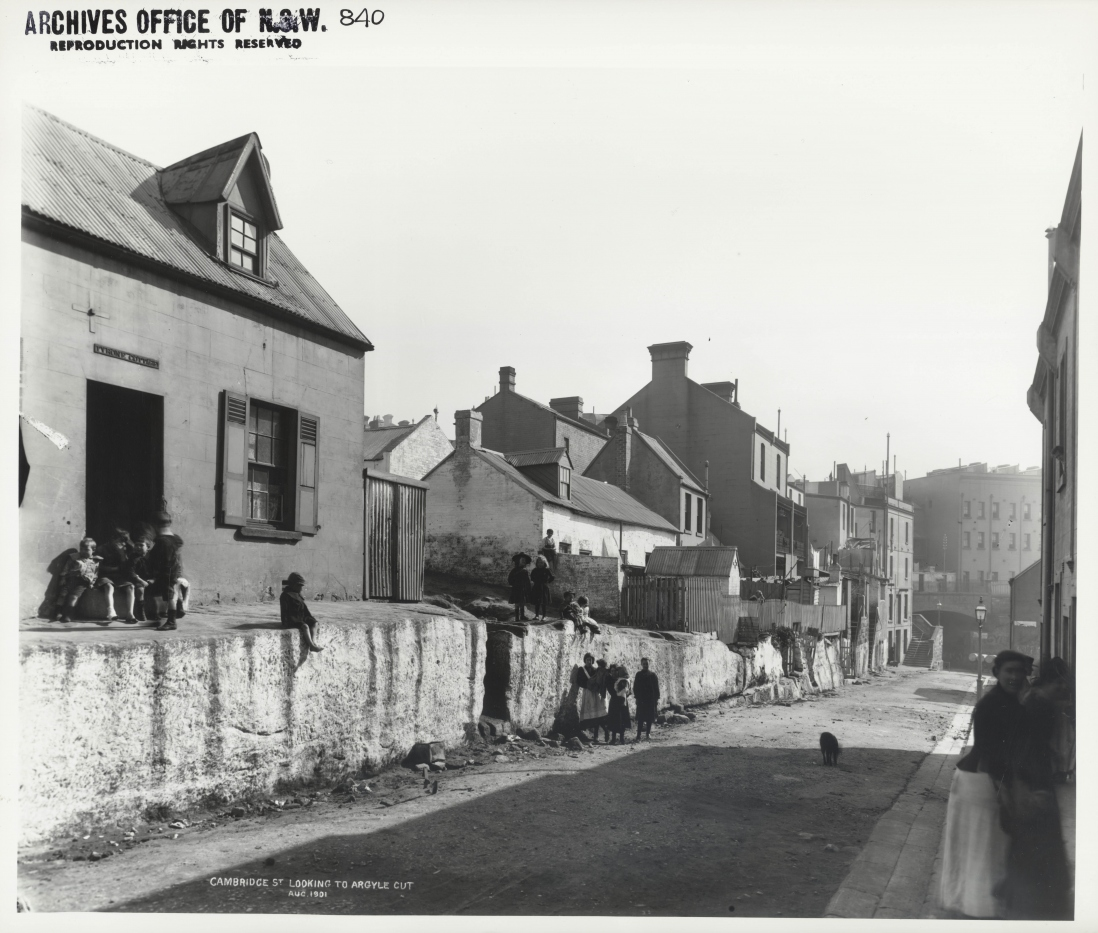 Photograph of street scene. Children and women stand outside or at the door of a row of small cottages.