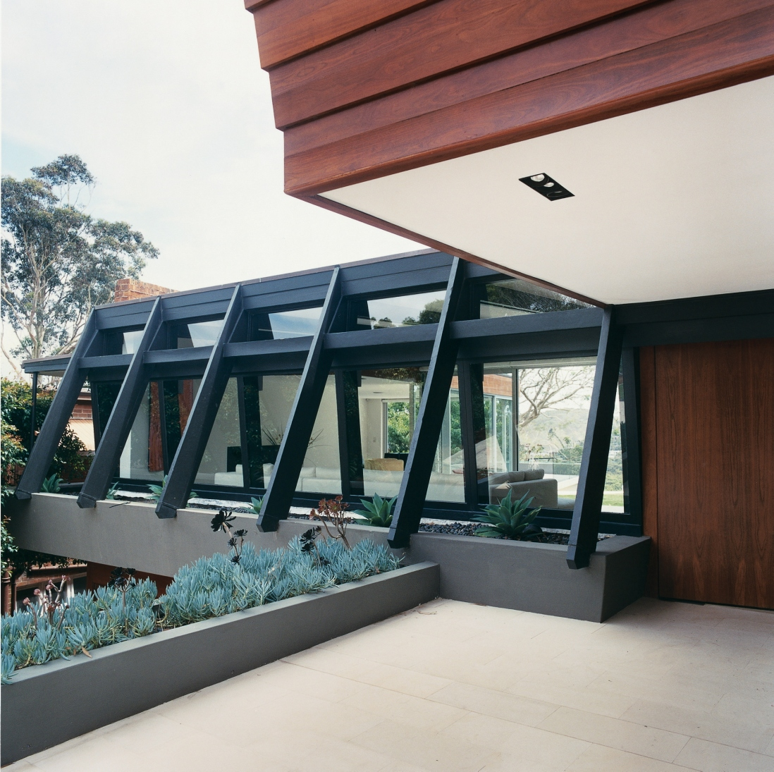 This is a photograph showing the detail of timber frames outside one set of windows with raised garden beds planted below