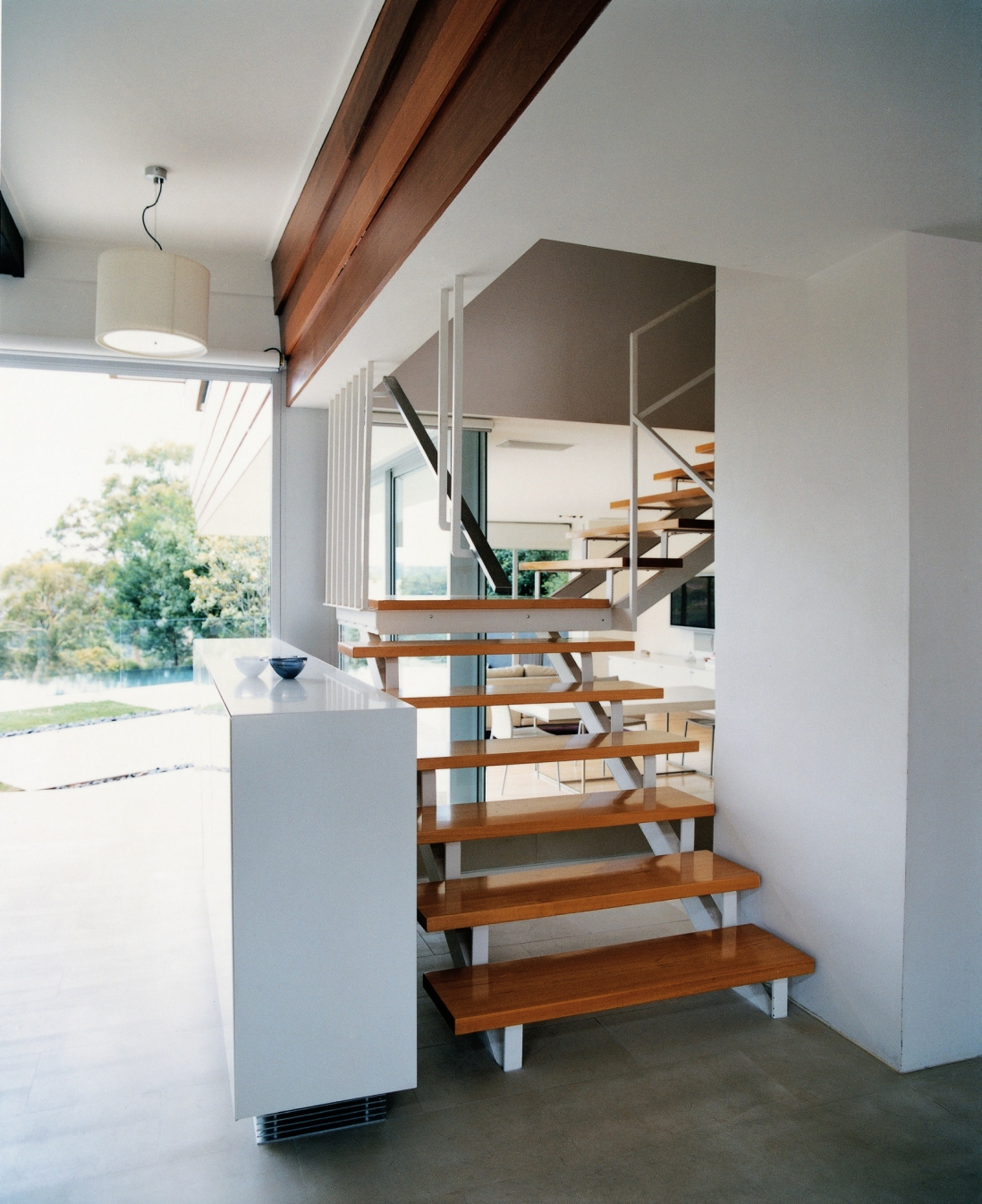 This is a photograph of a set of interior timber stairs on a white steel frame and open on each side