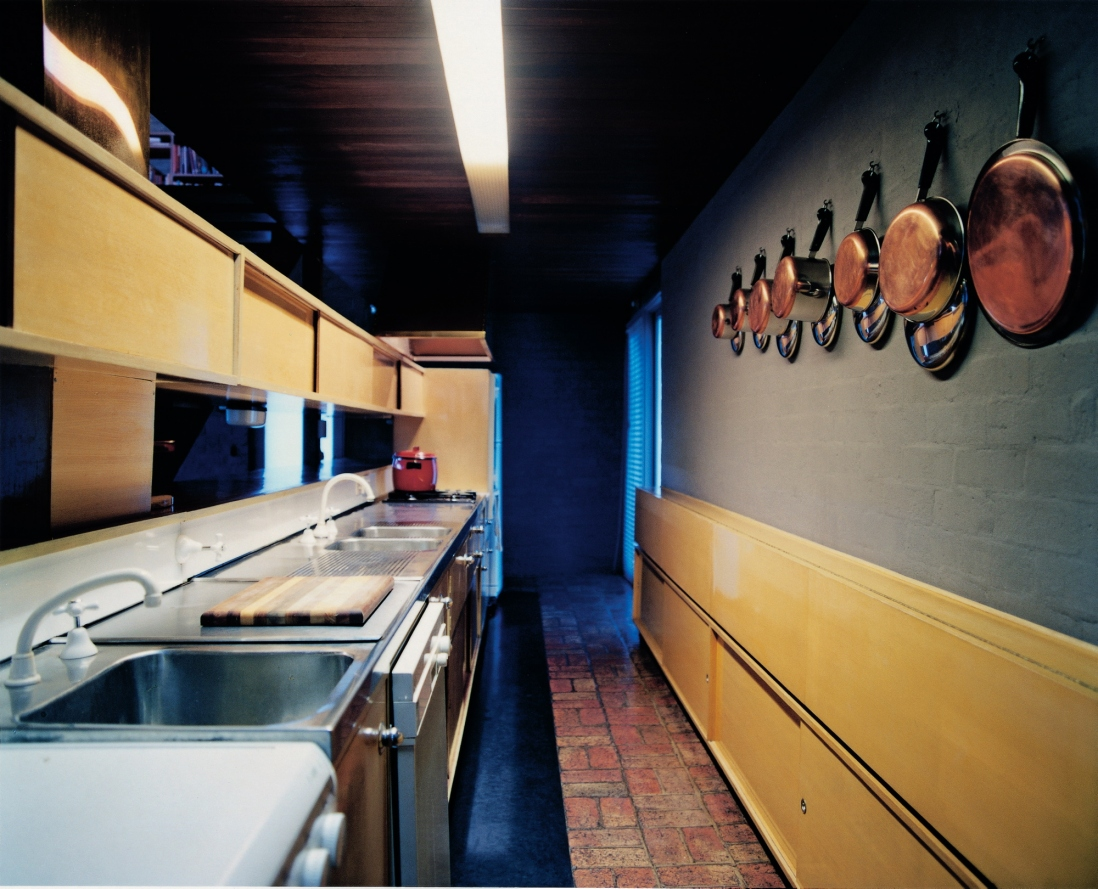 This is a colour photograph of a galley-style kitchen with dark blue walls, timber panelled cupboards, and kitchen pots hanging along one wall