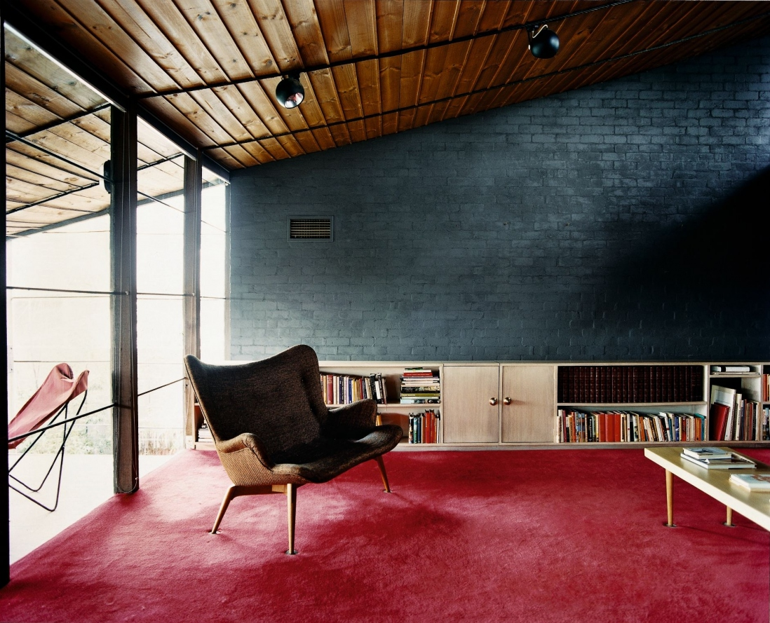 This is a colour photograph of a two seater couch in an open living space with deep red carpet and grey painted brick walls