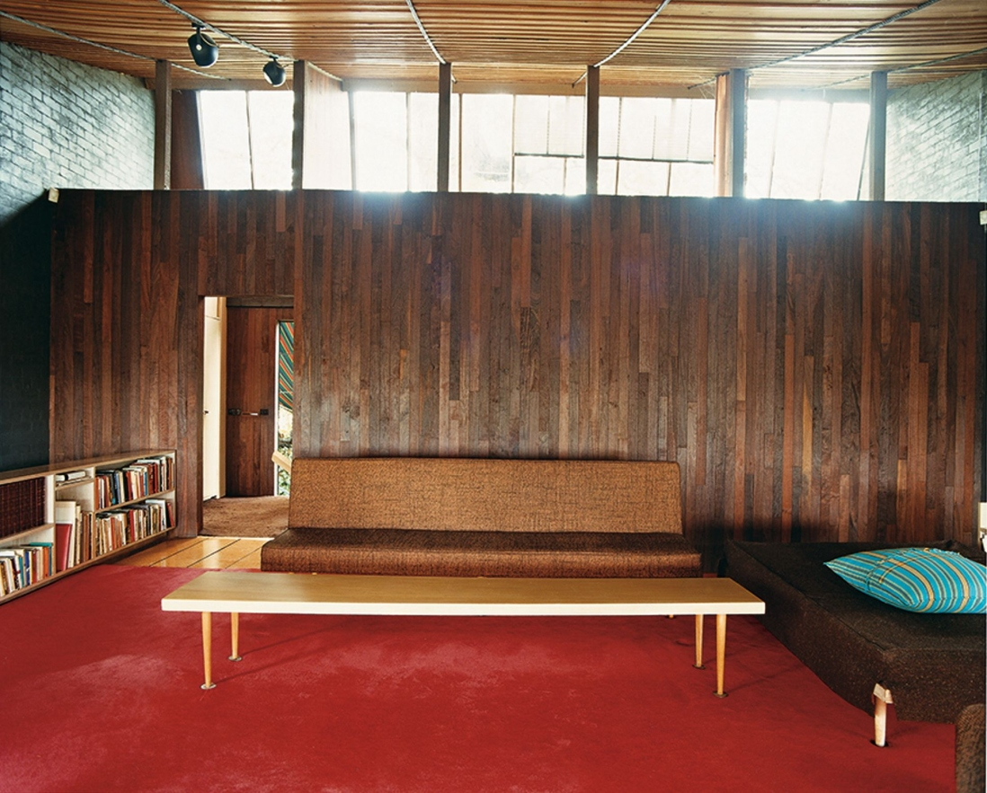 This is a colour photograph of a simple 1950s style sofa with a low timber coffee table in front with a deep red carpet floor and timber wall behind