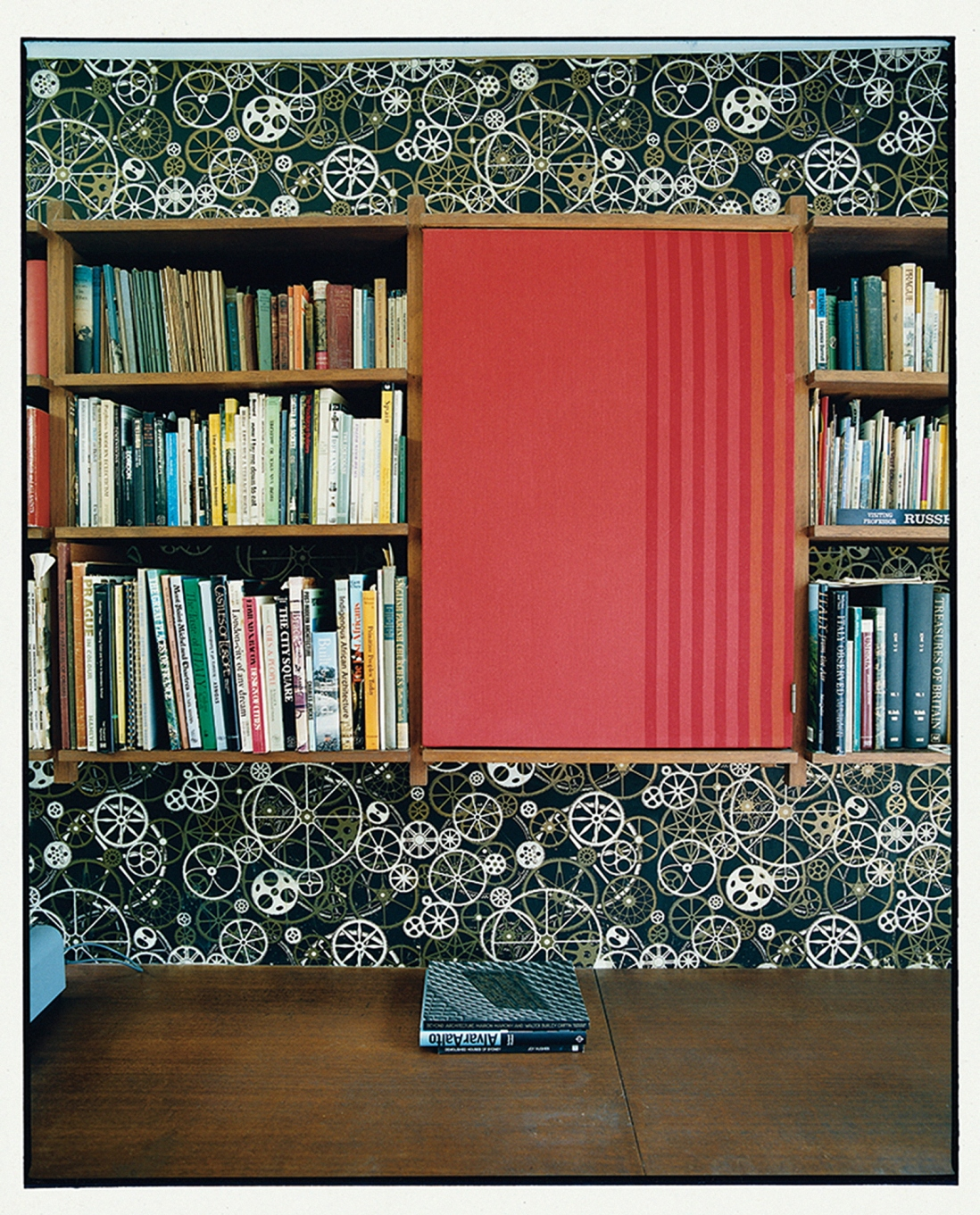This is a photograph of a wall with filled bookshelevs in the centre, black and white wallpaper at the top and bottom and a large red panel to the right