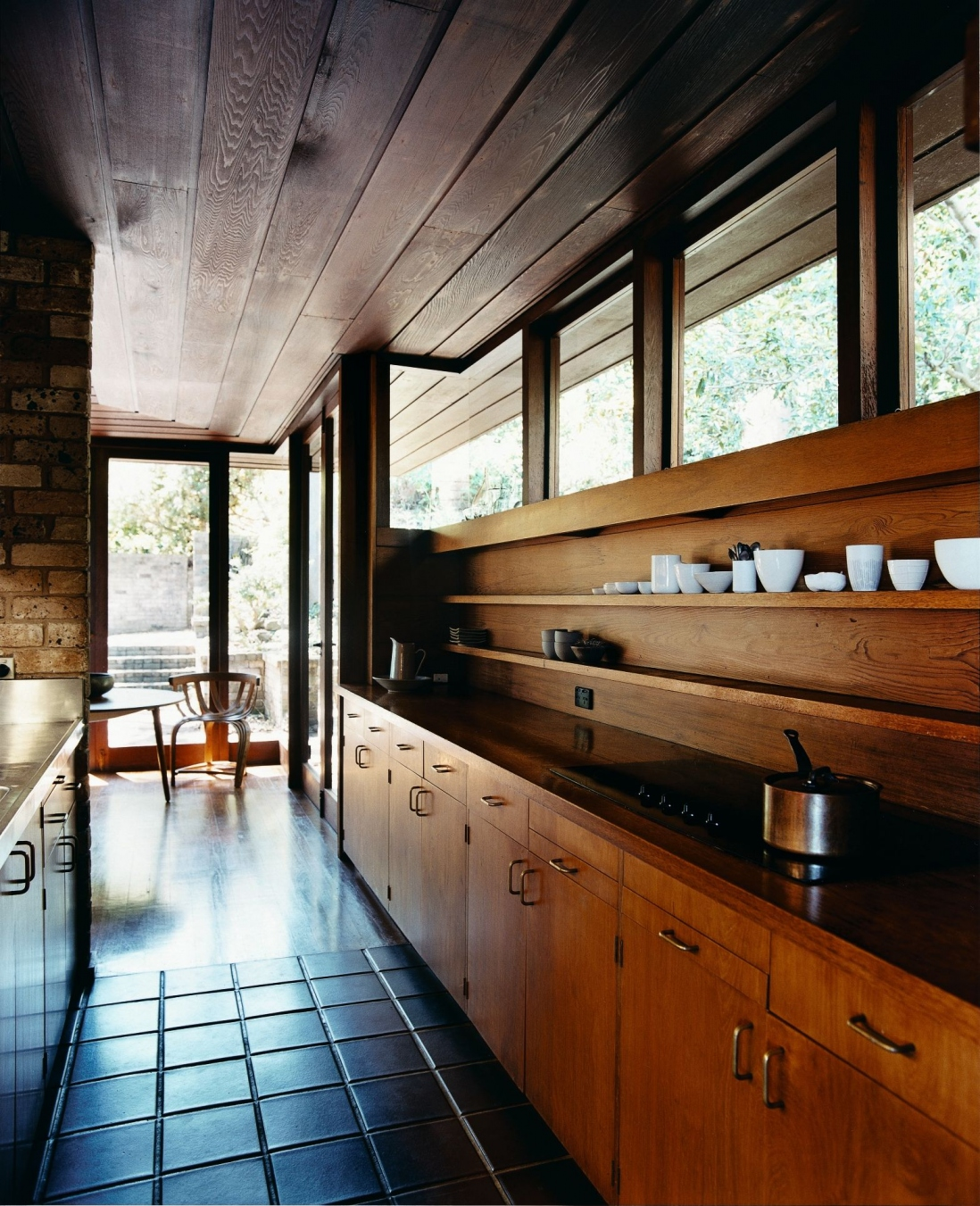 This is a photograph of a gallery style kitchen with a tiled floor. Timber is used for the ceiling, cupboards and benches.
