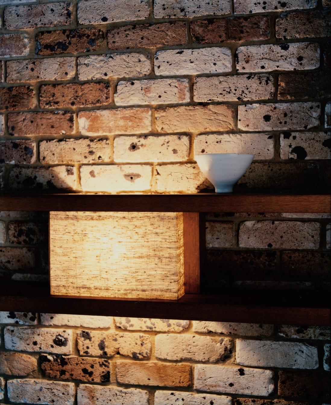 This is a detail photograph of a brick wall with two timber shelves. In one section between the two shelves a light has been created using a piece of linen.