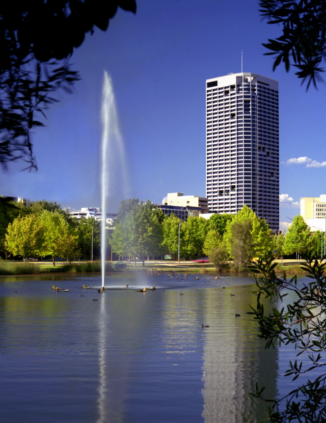 This is a colour photograph of an office tower with a wide river and fountain of water in the foreground