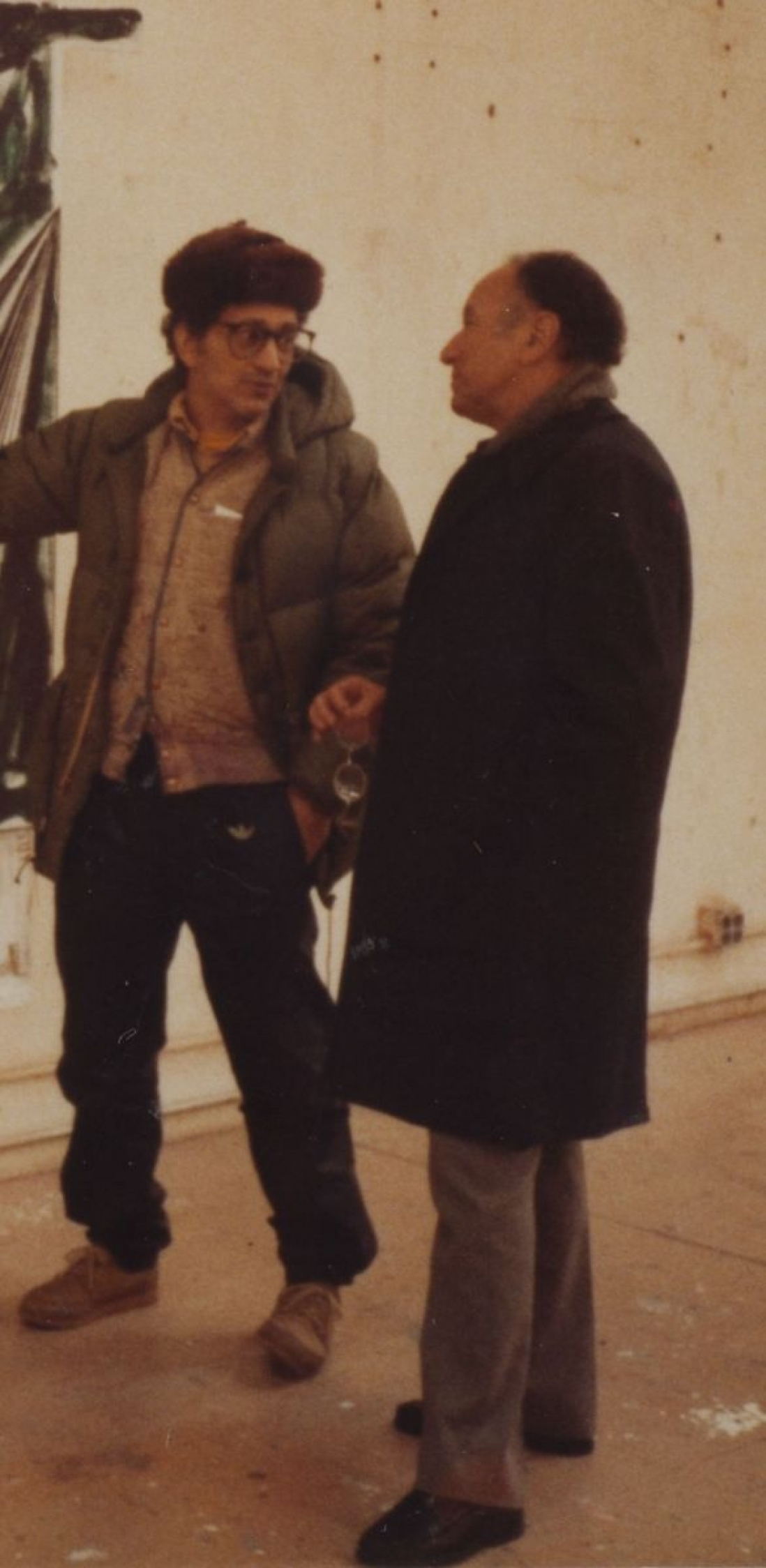 This is a colour photo of two men dressed in coats, one in a warm hat gesturing to something off screen, standing near a concrete wall