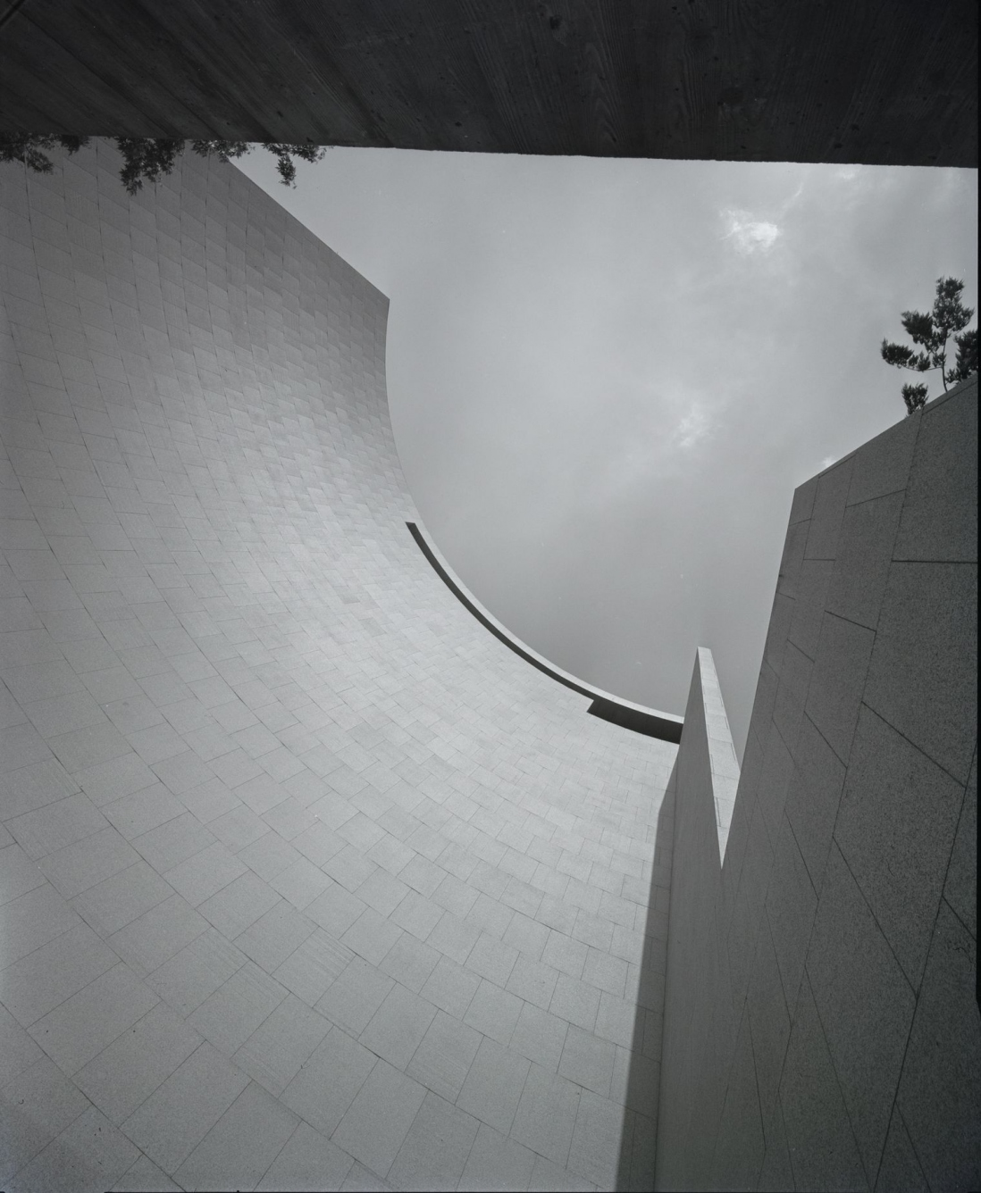 This is a black and white photo of a building facade shaped in a curved quadrant and taken from the base of the building looking up