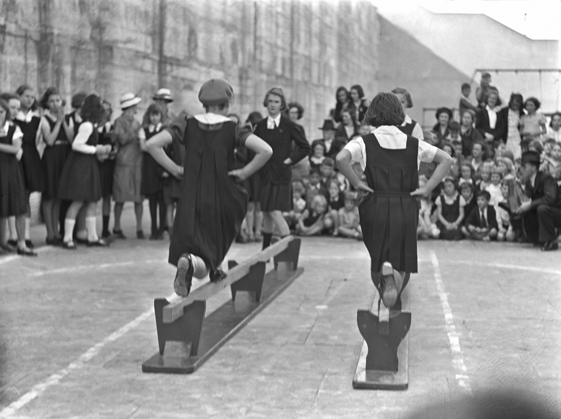 Black and white photo of children in black tunics doing exercises.