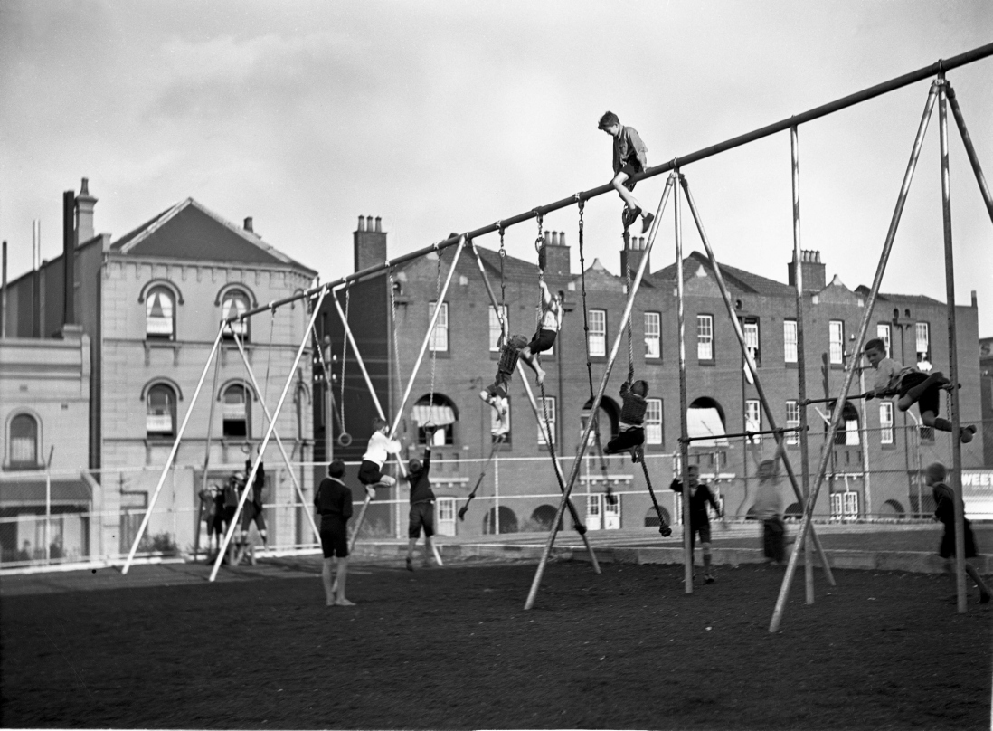 Black and white photo of children playing on equipment.