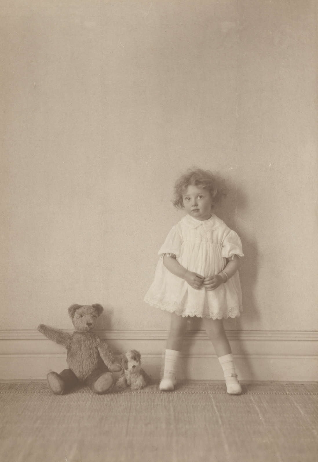 This is a black and white photograph of a little girl in a short white dress standing against a wall with a teddy bear and stuffed dog to her left