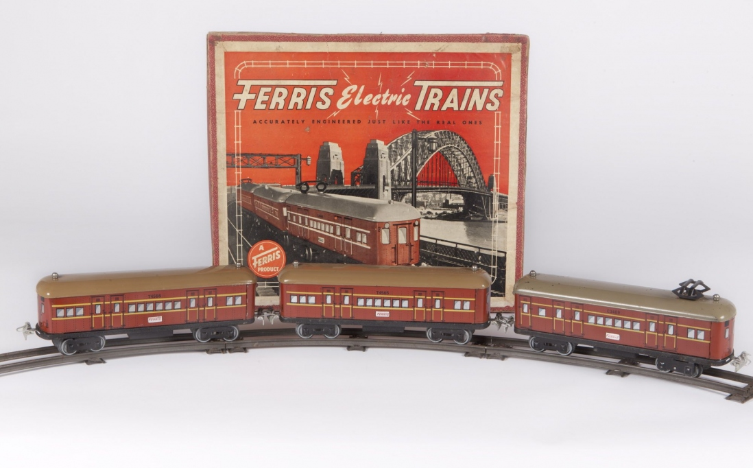 This is a colour photograph of three toy red train carriages on some track in front of a red box with a picture of the same carriage style train travelling across the Sydney Harbour Bridge