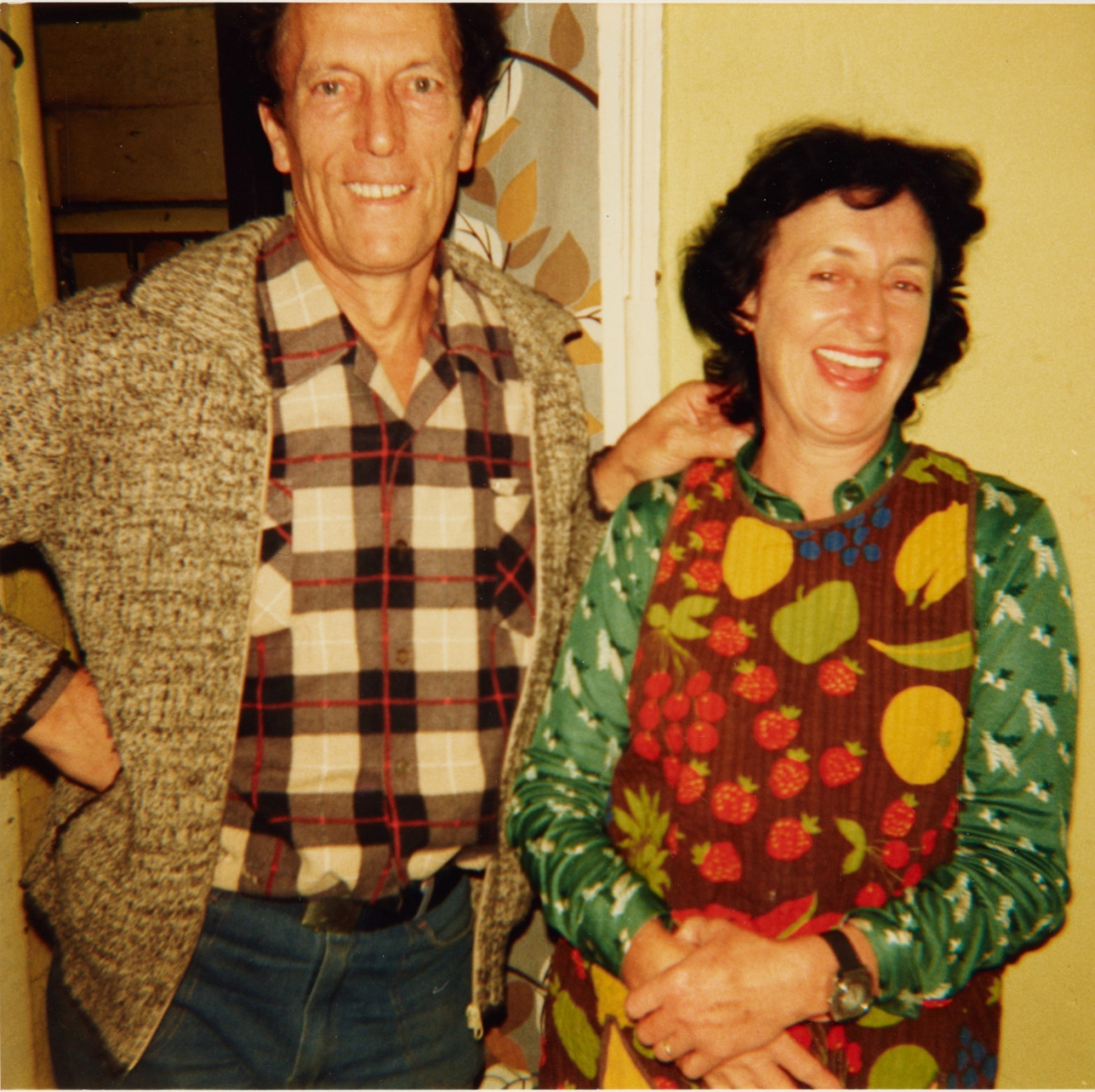 Man wearing cardigan and checked shirt (left) with woman wearing colourful top (right).