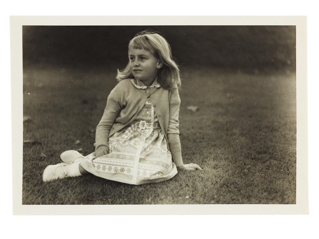 Black and white photo of young girl seated on ground with legs folder to her right.