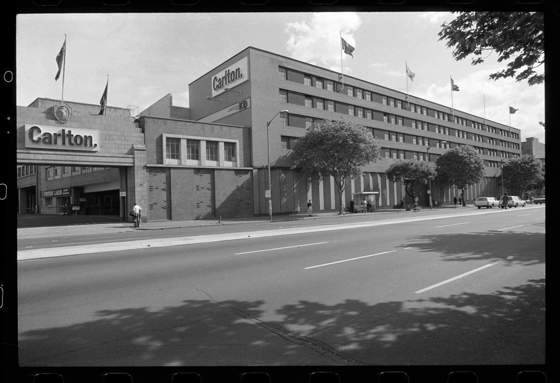 B&W image of a 5 storey building with 'Carlton' sign and logo above the vehicle entry. Flags are flown on the building.
