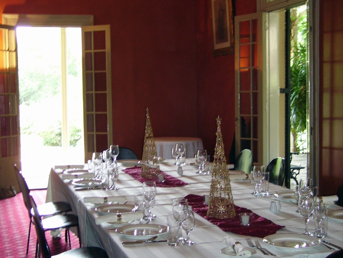 Ornate room with table set for meal with open doorway to sunlit verandah beyond.