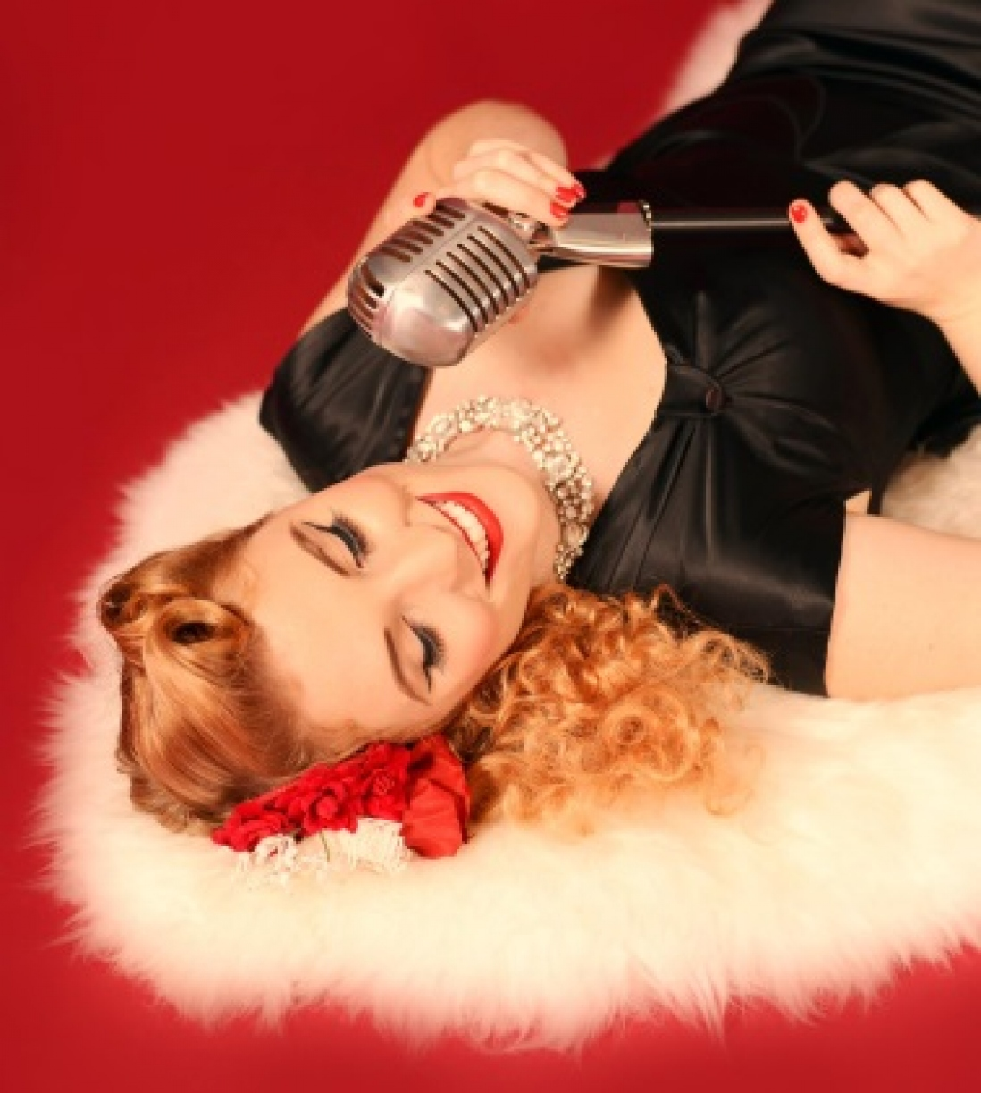 Photo of a woman lying on a rug with an old-fashioned microphone