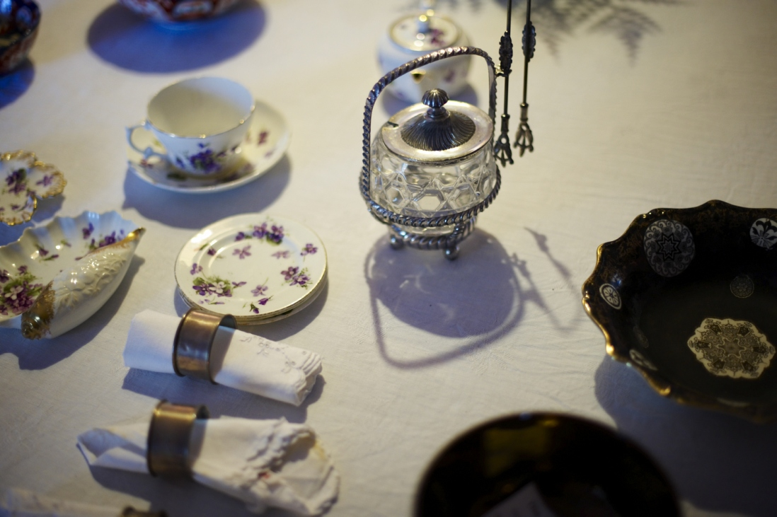 Table setting  including cups and saucers, bowls, cloth napkins, napkin rings, tongs and sugar bowl.
