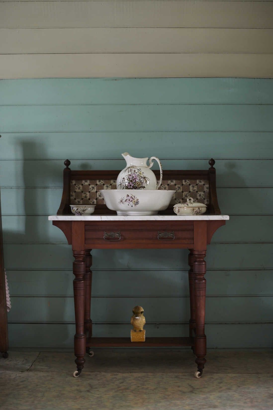 Wooden washstand with china jug, bowl and other items.