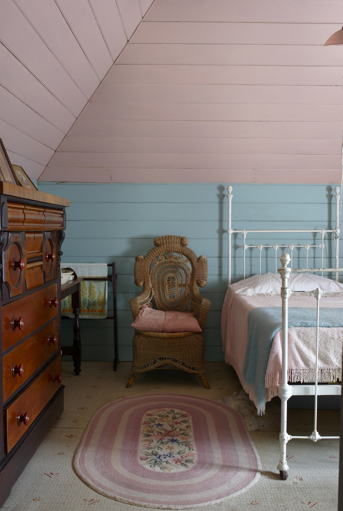 Pink and blue painted wooden room with single metal framed bed, next to armchair and chest of drawers.