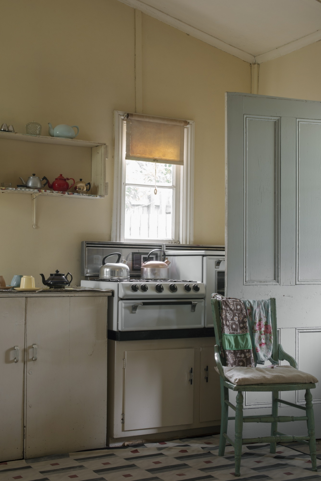 Interior of kitchen with backlit window over stove and open doorway to right.
