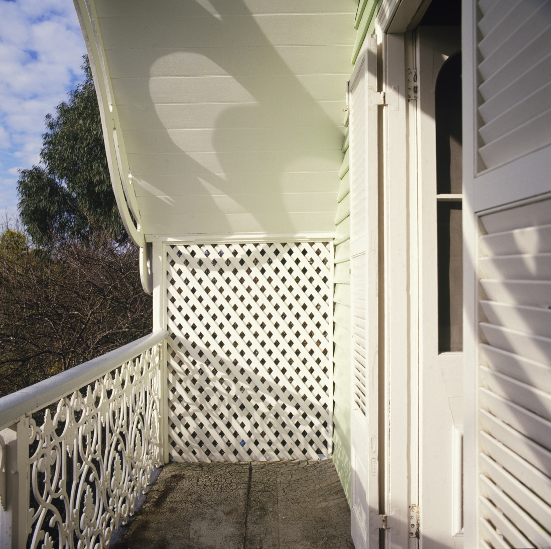 Sunlit balcony with ironwork handrail.