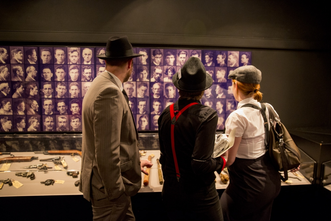guests looking at photographs of criminals at the Mayhem event, Justice and Police Museum