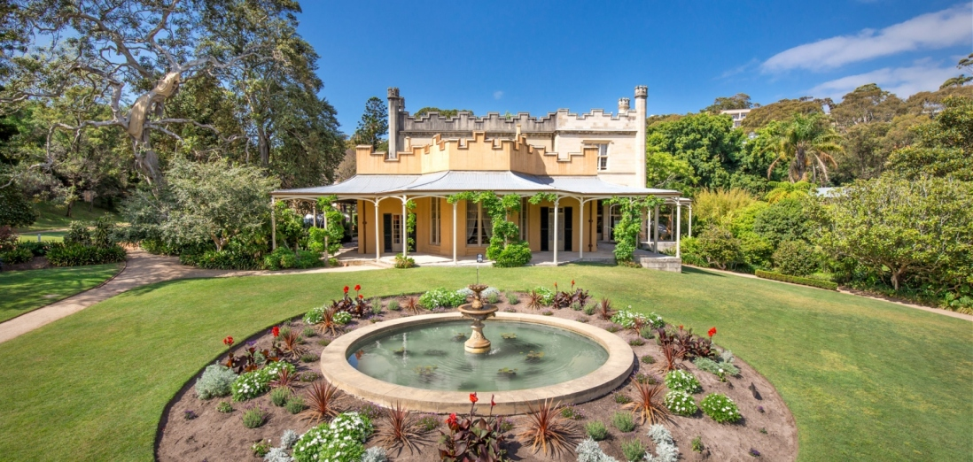 Front of heritage house with verandah, turrets and a fountain in foreground.