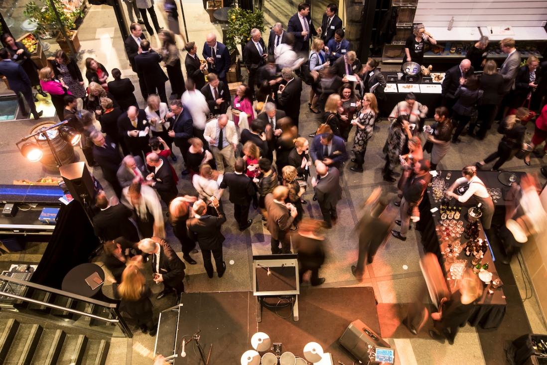 Large group of people having cocktails in foyer area.