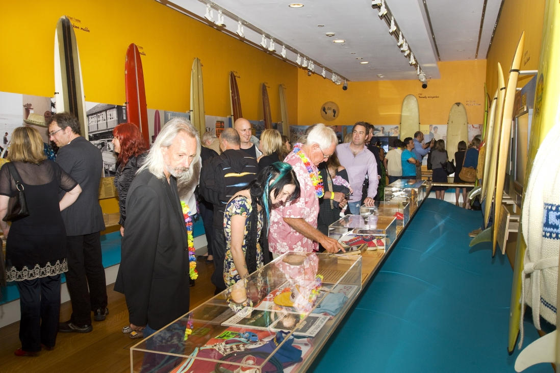 Crowds examining pieces at the Surf City exhibition opening