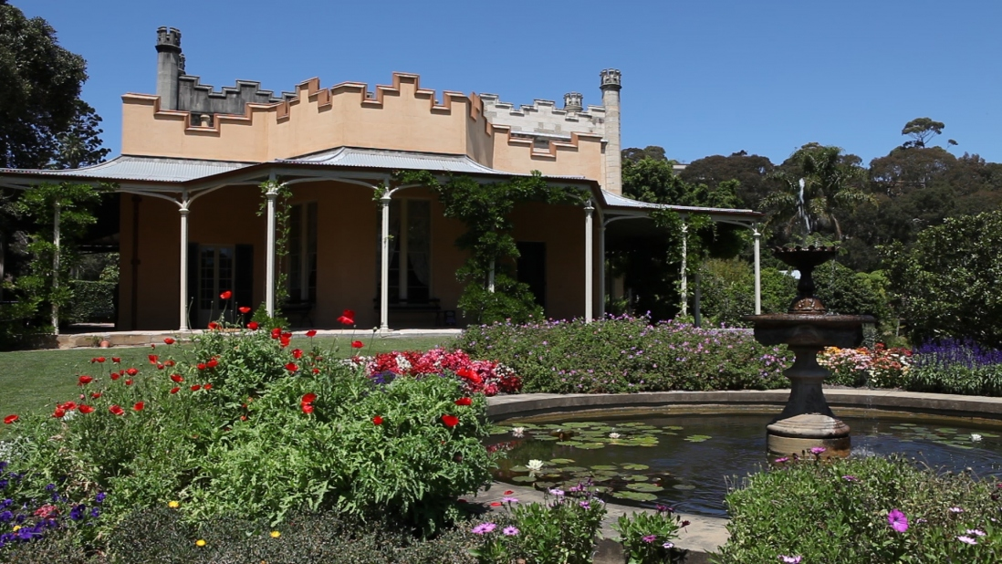 Image of the front of Vaucluse house with the gardens in full bloom. A fountain appears in the foreground squirting water.