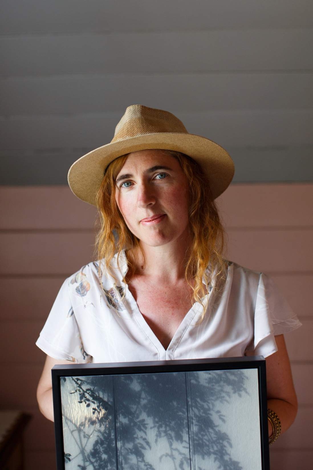 Women in straw hat and white shirt holding photographic artwork