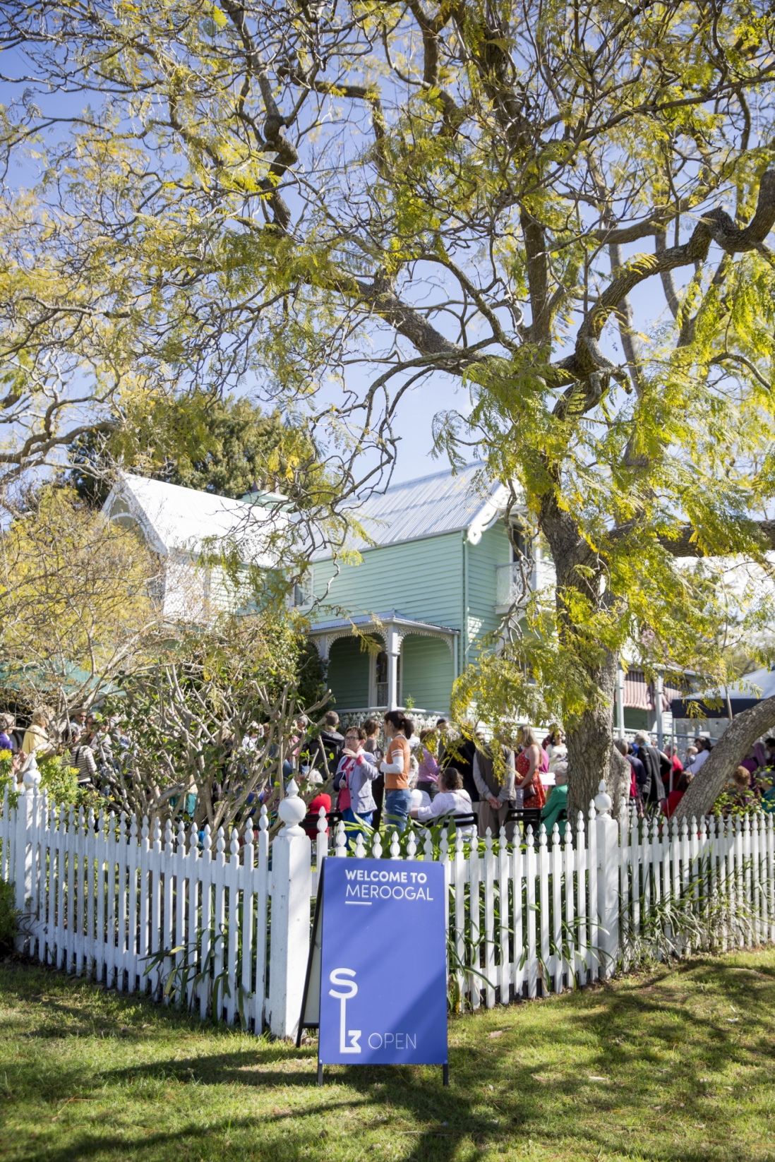 Exterior of green house with white picket fence and crowd of people in garden.