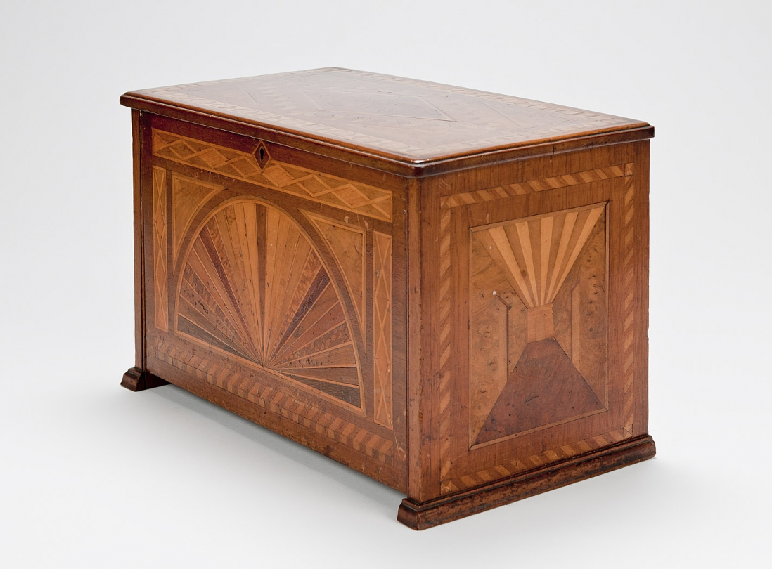 Wooden chest with inlaid pattern.