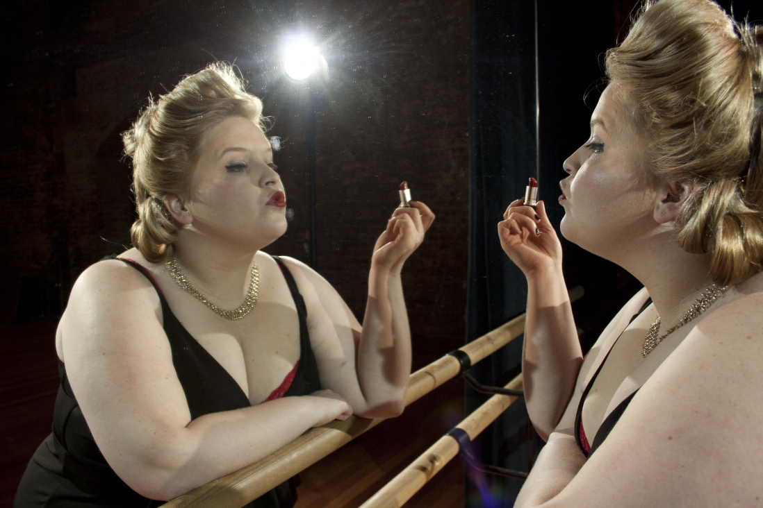 Woman standing in front of a mirror applying lipstick