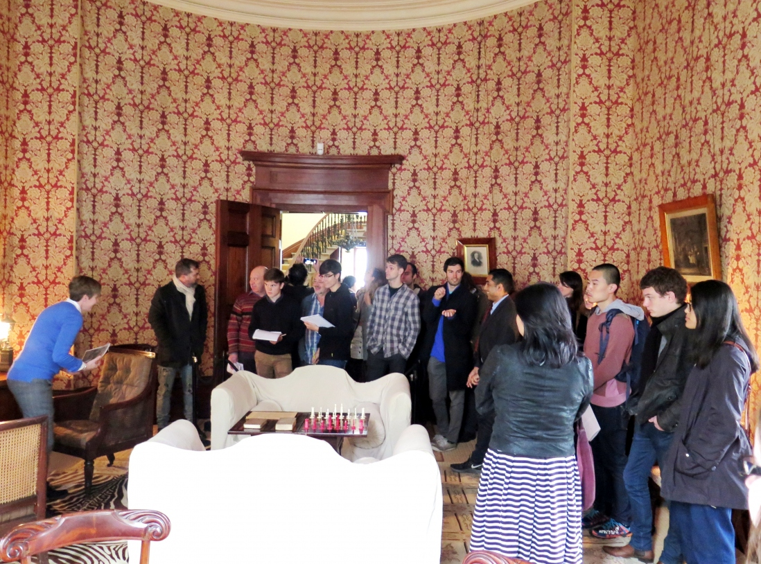 Group in room with patterned wallpaper.
