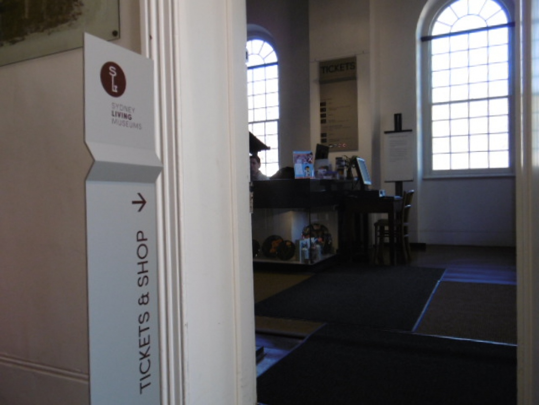 Sign in doorway to reception desk area, lit by large arched windows.
