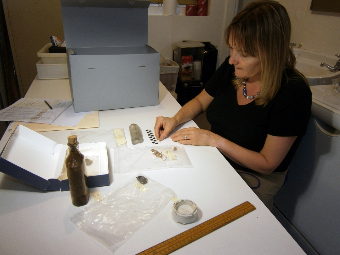Woman seated at table working with artefacts.