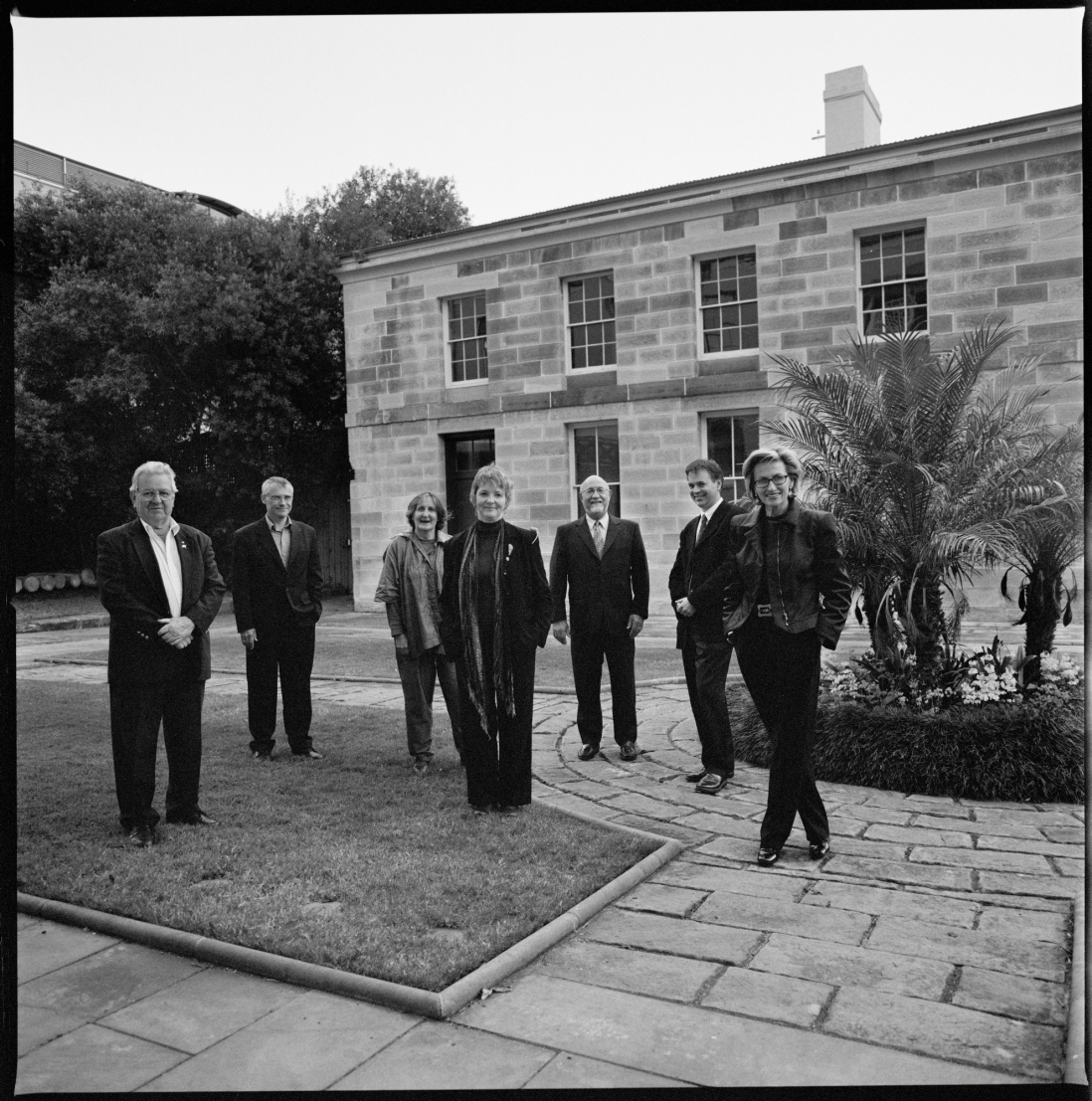 Black and white photo of group in sandstone courtyard.