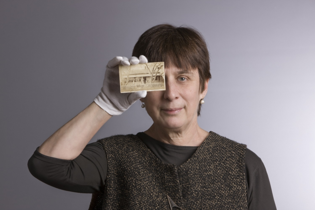 Head and shoulders photo of woman holding up card to face with conservator's white glove on hand.