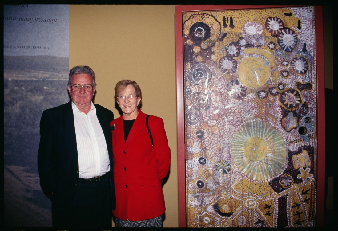 Man in black jacket and woman in red top in front of artwork.