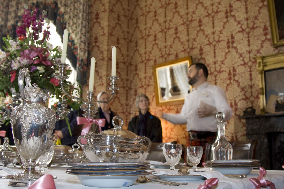 Man wearing kilt and white shirt standing in a wallpapered room in front of a richly decorated and set dining table at Elizabeth Bay House.