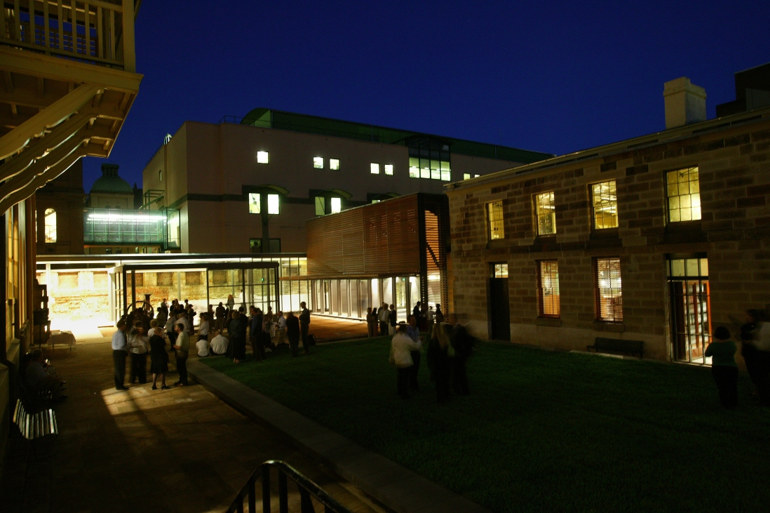 Photo of the mint buildings at night. People are standing inside silhouetted.