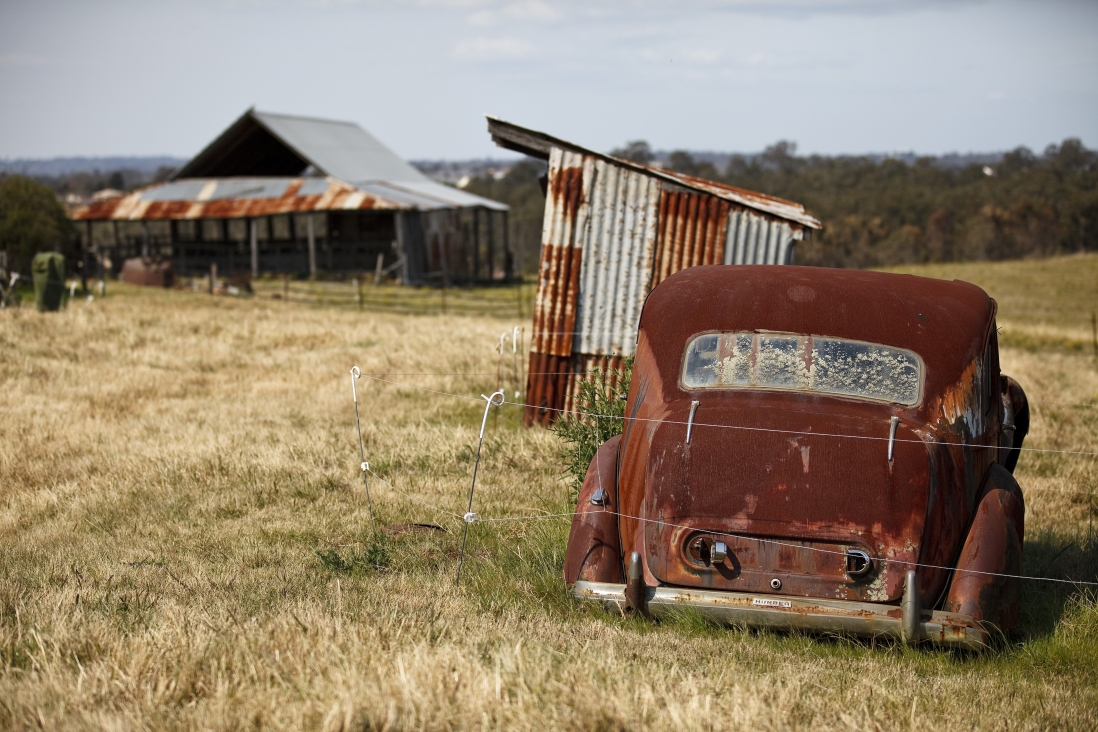 Looking towards the barn at Rouse Hill House and Farm, with the fuel shed and an old car in the foreground.