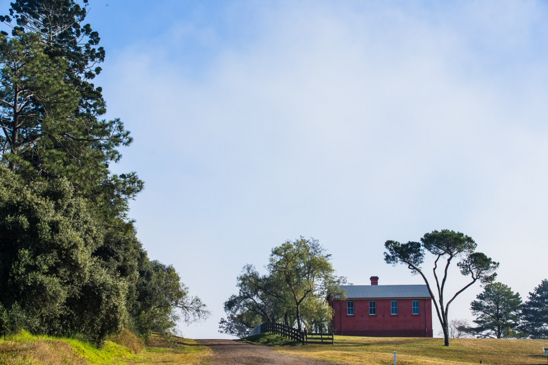 Red building with trees on hill.