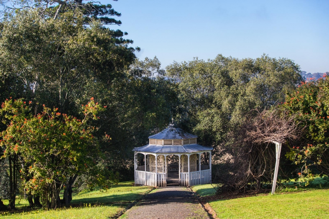White gazebo with pointed roof at bottom of pathway surrounded by trees.