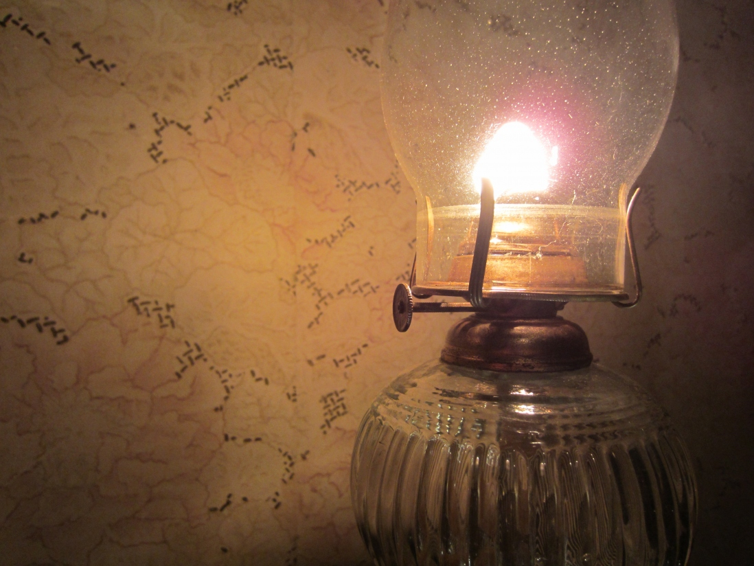 Closeup of kerosene lamp illuminating wallpaper behind.