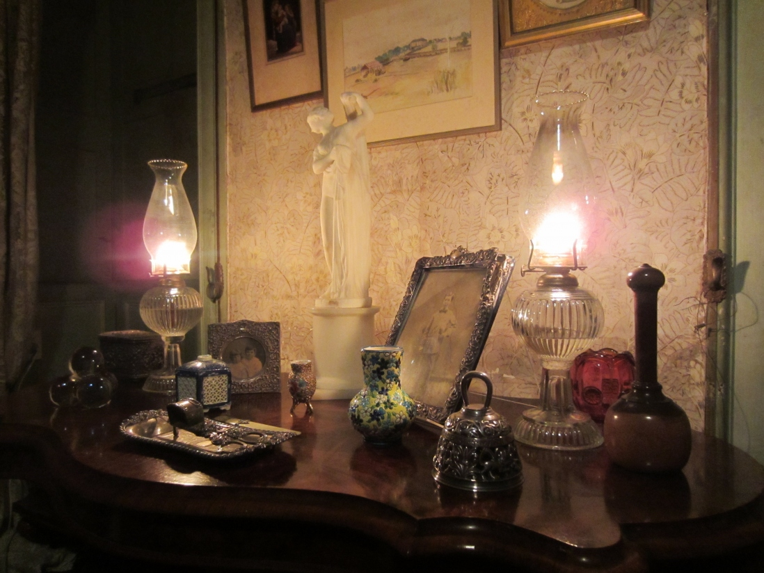 Kerosene lamps illuminating framed pictures, objects and wallpaper behind.
